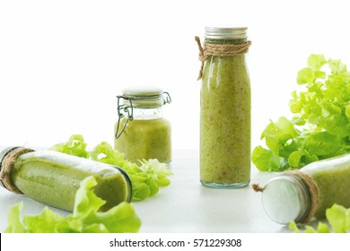 Mix green fruit and vegetable juice made from kiwi & green lettuce in glasses bottle wrapped by hemp rope laying on white table, raw organic fruit juice for healthy people, green juice for weight loss - Shutterstock ID 571229308