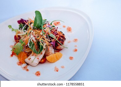 Mix green salad with seafood and orange on white plate, close up shot