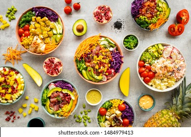 Mix of hawaiiajn Salmon and Tuna poke bowls in colorful bowls with fruits and vegetable around on light background. Top view, overhead, flat lay