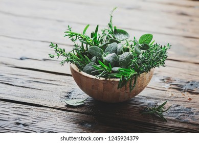 Mix of herbs: sage, thyme, rosemary on the wooden table, selective focus and toned image