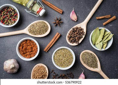 Mix of herbs and spices on dark stone table. Top view