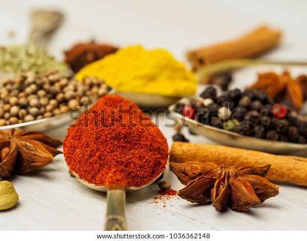Mix of Indian spices in spoons on white wooden table, side view, selective focus, macro. Seasonings paprika, close up