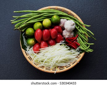 Mix ingredients of Thai green papaya (Som tum) salad composed of shredded papaya, tomato, lime, garlic, chili, and long bean in brown basket on dark background