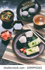 Mix of Japanese food - rice balls onigiri, omelette, ginger, sunomono wakame cucumber salad. Traditional dessert of bean and green tea matcha - jelly yokan, daifuku mochi. Asian breakfast or lunch