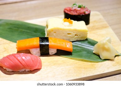 The mix of Japanese food sushi; salmon roll with rice, imitation crab meat roll with rice, sweet egg roll, and tuna sushi, on the wooden board served with leaf and ginger