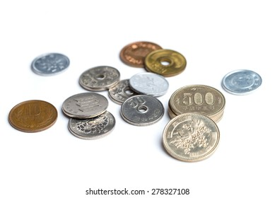 A mix of Japanese Yen coins spread out on a white background.