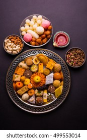 Mix Mithai and diya on diwali over colourful background