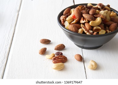 Mix nuts and dried fruits in the bowl put on the white painted wooden. Seen from side view and decorated with some nuts on the white wood. Food and snack concept.