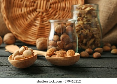 Mix of nuts in the glass jars and wooden spoon, on the table