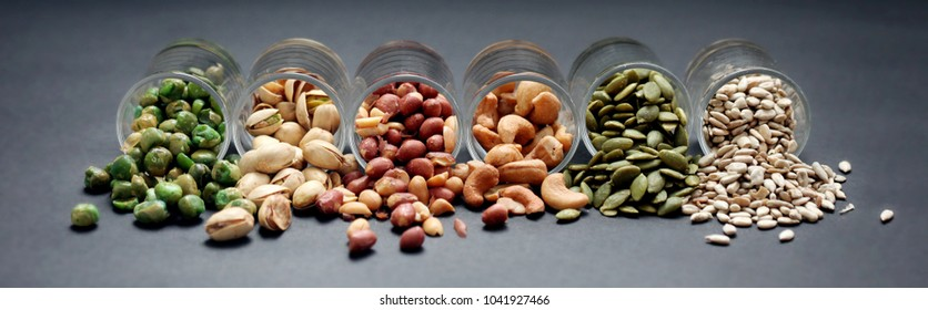 Mix Nuts in the glass on black background close up , peanut peas sunflower seeds  pumpkin seeds cashew nuts  pistachios