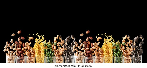 Mix Nuts in the glass on black background close up nuts pistachios almond cashew nuts peanut sunflower seeds