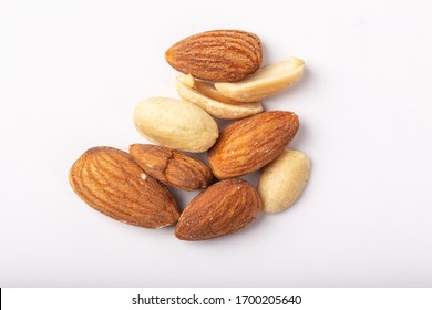 Mix nuts on Blue Background. Mixed nuts are a snack food consisting of any mixture of mechanically or manually combined nuts.