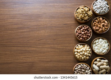 Mix of nuts on a wooden table. Almonds, cashew, peanut and hazelnuts in wooden bowls on wooden and burlap, sack background. Nuts.