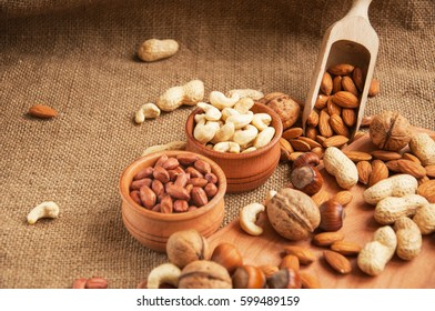 Mix of nuts on a wooden table. Almonds, cashew, walnuts, peanut and hazelnuts in wooden bowls on wooden and burlap, sack background. Nuts.