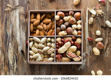 Mix of nuts: pistachio, almonds, hazelnut, peanuts  in vintage wooden box on rustic wooden background. Top view. Raw healthy food. Assorted of nuts