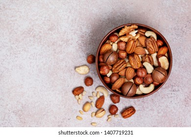 mix of nuts in a wooden bowl on a light background. view from above
