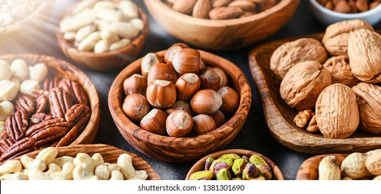 Mix of nuts in wooden bowls on dark stone table top panoramic view. Walnuts, cashew, almond, pistachio, pecan, hazelnut, macadamia nut. Healthy various super food selection with back light.