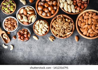 Mix nuts in wooden bowls on dark stone table top view. Almonds, pistachio, walnuts, cashew, hazelnut.