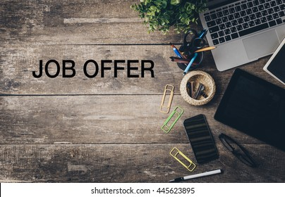 Mix of office supplies and gadgets on a wooden desk with text - job offer