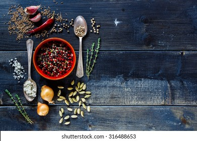 Mix of peppercorn in ceramic bowl, herbs and spices selection over dark old wooden background with space for text. Food or cooking concept