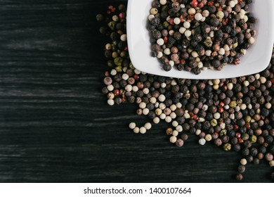 Mix of peppercorns in white bowl on wooden background. Red, black, green and white pepper