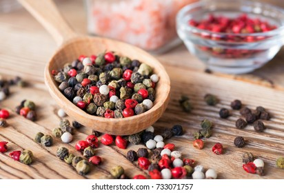 Mix of peppercorns in wooden spoon on rustic background with pink salt in glass jar. Red, black, green and white dry pepper in seeds.