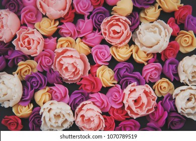 Mix of pink and Peach Fake Plastic Mini rosess Flowers Black Background copy space. Craft, Art, Hobby concept.