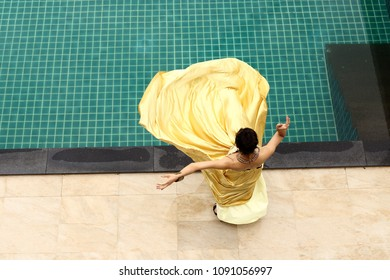 Mix Race Tanned Skin Woman in Yellow Gold Fashion Evening Gown Dress on the Edge of Swimming Pool, Top View from Above, Happy feeling of Perfect Holiday Vacation Summer, Copy Space Text Logo