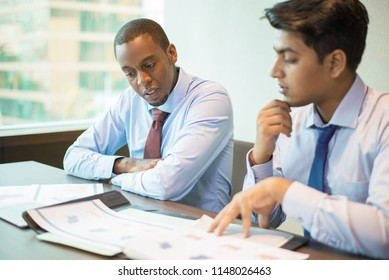 Mix raced business group analyzing reports and planning next sales period. Indian and Afro American men in formal shirts and ties studying graphs and charts at meeting table. Marketing concept