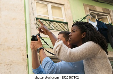 Mix raced couple of tourists going sightseeing outside. Young man and woman standing in old town street, pointing finger away and taking picture. Photography concept