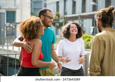 Mix raced group of people having fun and spending great time outdoors. Close interracial friends meeting on outdoor building terrace, hugging, chatting and laughing. Friendship and leisure concept