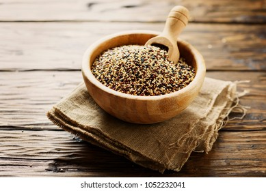 Mix of raw red, white and black quinoa on thw wooden table, selective focus