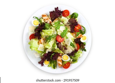 Mix salad with grilled chicken, parmesan cheese, cherry tomato and quail eggs. Top view on white plate. Isolated on the white background.
