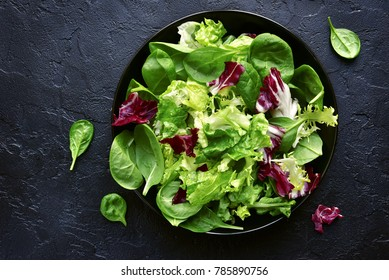 Mix salad leaves in a black bowl over dark slate, stone or concrete background.Top view with copy space.