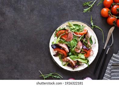 Mélanger la salade avec des tomates et du boeuf moyen dans une assiette sur fond noir.
