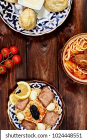 Mix set foods top view on table. Plov, noodle, meat, manti, tomato. Space for text. Caucasian restaurant concept