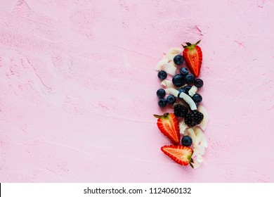 Mix of smoothie or breakfast ingredients flat lay. Organic strawberry, blueberry, blackberry and coconut chips on pink background, superfood and detox concept. Top view