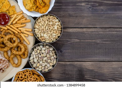 Mix of snacks for beer on dark wooden background. Top view. Empty space for text