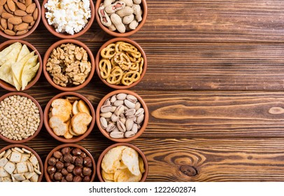 Mix of snacks : pretzels , crackers , chips , nuts and nachos