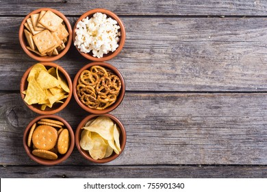 Mix of snacks : pretzels  crackers  chips  nuts  popcorn and nachos - Shutterstock ID 755901340