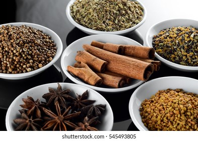 Mix Spice anise aniseed cinnamon fenugreek in white bowl over black background