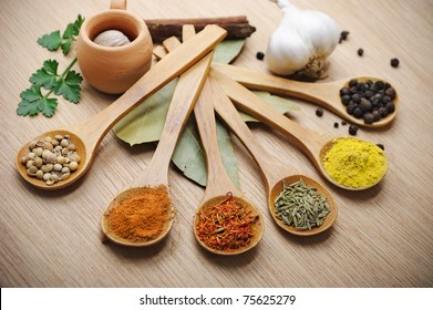 mix of spices in wooden spoons