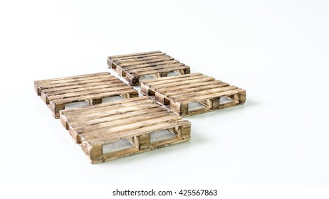 Mix stack of miniature wooden pallet. Concept of shipping and logistics. Isolated on white background. Slightly de-focused and close-up shot. Copy space.