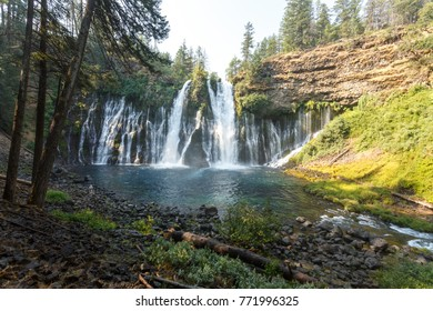 Mix of sun and shadows fall on wide, beautiful McArthur-Burney Falls flowing fast and  full off the cliffs into a lake in Lassen Volcanic National Park's alpine forest