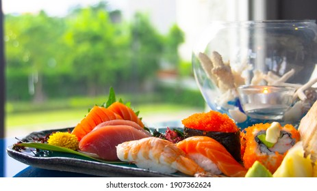 Mix sushi and sashimi plate on the table that could see outdoor and green garden. Japanese dish at the window