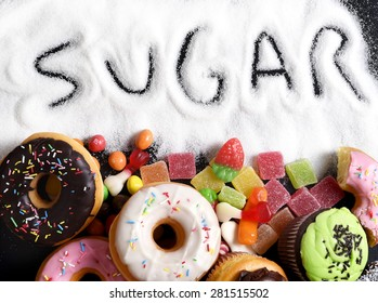 mix of sweet cakes, donuts and candy with sugar spread and written text in unhealthy nutrition, chocolate abuse and addiction concept, body and dental care