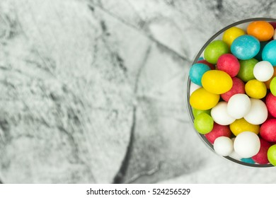Mix of sweet fruit candies in glass jar on grey background. Gift for special occasion: wedding, birthday, baby shower and others. Selective focus. Top view.
