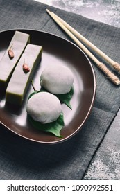 Mix of Traditional Japanese sweets - daifuku mochi (sweet paste anko wrapped around with soft rice mochi shell) and jelly dessert yokan (made of beans, agar, sugar and green tea matcha).