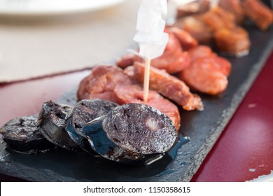 A mix of traditional Portuguese tapas - morcela, a black blood pudding, pork chorizo with paprika, thin and spicy linguica and garlic flavoured alheira sausage