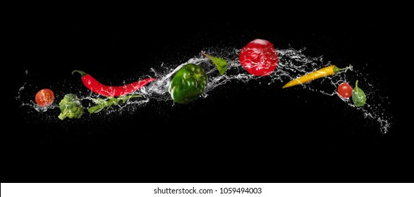 Mix of vegetable pieces in water splash, isolated on black background. Very high resolution image
